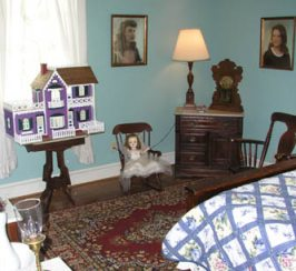 One of the bedrooms, which has a dollhouse under the window
